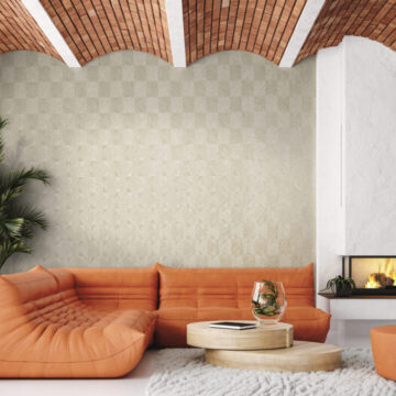 Modern living room loft with orange leather sofa and brick ceiling